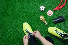Table top view aerial image soccer or football tournament season background. Flat lay player wear shoe with gold medal & ball on the artificial green grass Royalty Free Stock Image