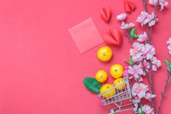 Table top view of arrangement decoration Chinese new year & lunar holiday background. Concept.Orange in shopping cart or trolley with accessories on modern red Royalty Free Stock Photos