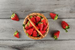 Table top view - basket with strawberries, some spilled on the g. Ray wooden desk stock image
