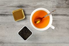 Table top view on cup of hot amber tea with spoon, and caddy full of black dried loose leaves, placed on gray wood desk. royalty free stock photo