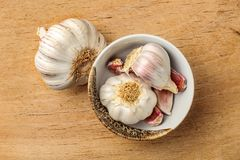 Table top view on garlic bulbs and cloves in small ceramic bowl,. Placed on old wooden cutting board Stock Photography
