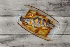 Table top view on grilled trout with orages in glass baking pan, stock images