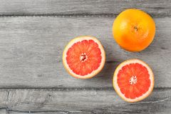 Table top view on red grapefruits, on cut in half, placed on gray wood desk. stock photos