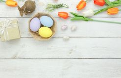 Table top view shot of decoration Happy Easter holiday. Background concept.Flat lay bunny egg with tulip flower and rabbit doll on modern white wooden at office Royalty Free Stock Photo