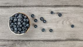 Table top view - small bowl of blueberries, some of them spilled. On rustic desk Stock Photography