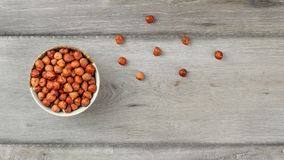 Table top view on small bowl full of hazelnuts on gray wood desk stock photography