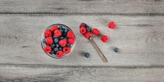 Table top view on small glass bowl filled with mix of blueberrie. S and raspberries, silver spoon on the side, placed on gray wood desk Royalty Free Stock Photo