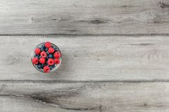 Table top view on small glass bowl full of blueberries and raspberries on gray wood table. royalty free stock image