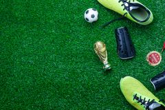 Table top view of soccer or football world cup season background. Flat lay accessories trophy & ball with shoe on the artificial green grass wallpaper.Free stock images