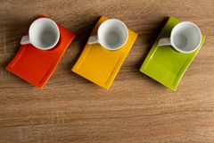 Table top view of three white coffee cups placed on coloured dishware. stock image