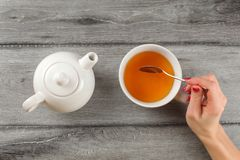 Table top view - woman hand holding spoon, stirring tea in white. Porcelain cup royalty free stock images