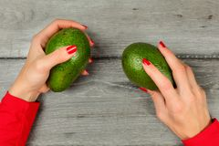 Table top view on woman hands with red nails, holding two green. Whole avocado over gray wood desk stock photography