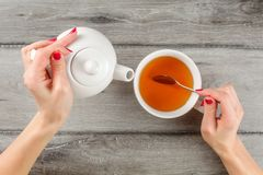 Table top view on young woman hands holding white ceramic teapot. In one and silver spoon above cup of hot tea in other royalty free stock photo