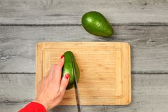 Table top view - young woman hands with red nails holding knife, cutting avocado on chopping board. royalty free stock photos