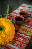 On the table, on a towel with a national ornament clay cups of tea. Next to the flower of a sunflower. Royalty Free Stock Photo