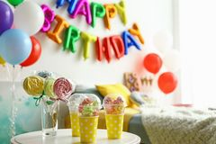 Table with treats and phrase HAPPY BIRTHDAY made of colorful balloon letters in modern bedroom