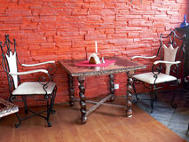 Table for two. A restaurant table set at a red brick wall Royalty Free Stock Image