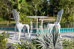 Table and two chairs next to the pool Royalty Free Stock Images