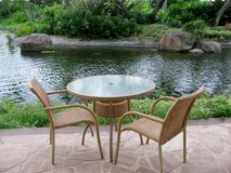 Table and  two chairs on an outside patio by a pond Stock Images