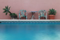 TABLE AND TWO CHAIRS POLSIDE. Beside the pool, some plants, a table and two chairs Royalty Free Stock Photo