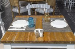 Table with two empty inverted plates in a restaurant. Greece Royalty Free Stock Photo