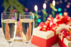 On the table are two glasses of champagne. near there are New Year`s gifts. background - burning candles on a dark blue background Stock Image