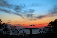 Table with two glasses of wine on sunset on sea. Outdoor Royalty Free Stock Photos