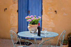 Table for two set with red wine. Provence, France. Table for two set with red wine in front of a rustic country house. The wall is painted in ochre with wooden royalty free stock images