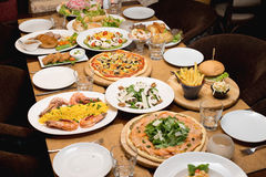 Table with various food plates served Royalty Free Stock Photography