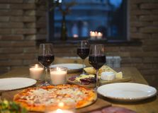 Table with various food served with red wine. And candles stock photos