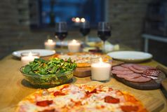 Table with various food served with red wine. And candles royalty free stock image