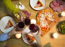 Table with various food served with red wine and candles. Top view. Toast of the friends royalty free stock images