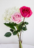 Table vase with bouquet of flowers. Red, pink poses with white hydrangea in the clear vase on the table Stock Photos