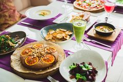 Table with vegetarian dishes - pizza, salads, pie and drinks. Food in restaurant. Table with vegetarian dishes - pizza, salads, pie and drinks Royalty Free Stock Photo
