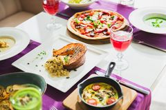 Table with vegetarian dishes - pizza, salads, soup, pie and drinks. Food in restaurant. Table with vegetarian dishes - pizza, salads, soup, pie and drinks Stock Photography