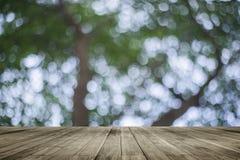 Table vide de conseil en bois devant le fond brouillé naturel Bois brun de perspective au-dessus de bokeh d'arbre photographie stock