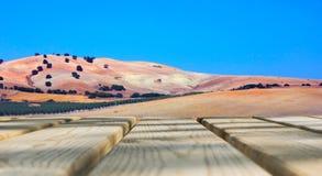 Table vide de conseil en bois devant le fond de ciel bleu et de montagne Plancher en bois de perspective au-dessus de champ et mo Image stock