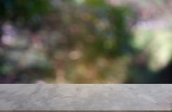 Table vide de marblestone devant le vert brouillé abstrait du fond de lumière de jardin et de nature Pour l'affichage de produit  photographie stock libre de droits