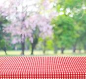 Table vide et nappe rouge avec le bokeh de feuilles de vert de tache floue, pour Photo libre de droits