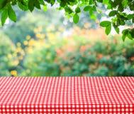 Table vide et nappe rouge avec le dos de bokeh de feuilles de vert de tache floue Photos libres de droits