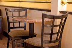 Table vide pour deux et mur jaune photo libre de droits
