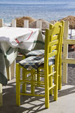 Table with a view. Two bright yellow chairs on a restaurant by the beach of Perissa, Santorini, Greece Royalty Free Stock Photos