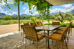 Table in vine-covered pavillion next to magnificent mountains Royalty Free Stock Photo