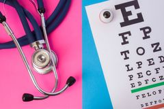 Table for visual acuity test Snellen chart and medical stethoscope is in two colors background: blue and pink. Concept of eye di. Agnosis in men and women Royalty Free Stock Image