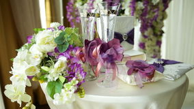 Table for a wedding ceremony with glasses of champagne, rings and a bouquet of flowers stock footage