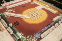 Table where Mahjong - the Mandarin tile-based game - is being played on a colorful mahjong mat with a dice in the middle - stock images