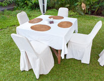 Table with a white cloth and 4 chairs. On a green lawn Royalty Free Stock Image