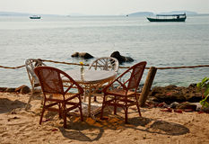 Table with wicker chairs on seacoast Royalty Free Stock Photo