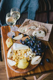 Table with wine, cheese, bread, grapes and pears Stock Photos