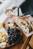 Table with wine, cheese, bread, grapes and pears Royalty Free Stock Image